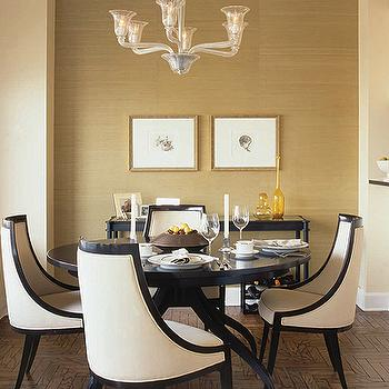 Elle Decor - dining rooms - black and white chairs, black and white dining chairs, gold grasscloth, gold grasscloth wallpaper, dining room accent wall, gold accent wall, parquet wood floors,