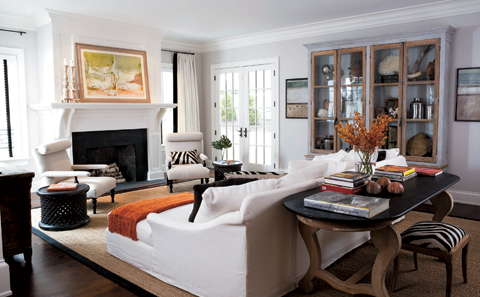 living rooms - white sofa modern slipper chairs walnut console table fireplace orange throw zebra bench gray walls sisal rug brown ribbon border trim French doors white cotton drapes black ribbon trim