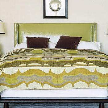 House Beautiful - bedrooms - green headboard, green wingback headboard, patent leather headboard, green patent leather headboard, vinyl headboard, green vinyl headboard, green and brown bedroom, green blanket, brown velvet pillows, buddha lamps, buddha table lamps,