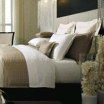 Kelly Hoppen Interiors - bedrooms - decorative coral, coral in vases, white and tan bedding, silk duvet,  Tufted upholstered leather headboard