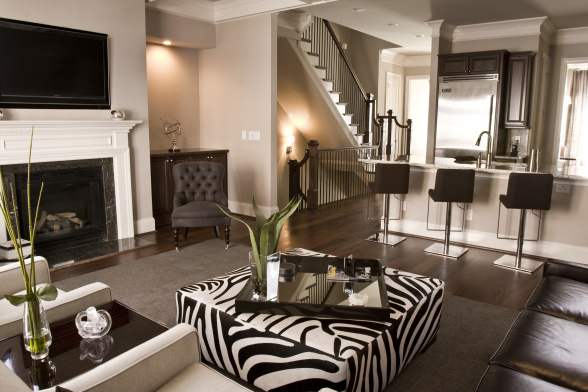 HGTV - living rooms - Sherwin Williams - Versatile Gray - Gloria Chair, gray walls, gray paint, gray paint colors, versatile gray, zebra ottoman, black and white zebra ottoman, brown rug, brown tufted chairs, open floor plan,