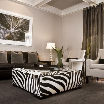 HGTV - living rooms - gray walls, gray paint, gray paint colors, versatile gray, zebra ottoman, black and white zebra ottoman, brown leather sofa, brown rug, taupe pillows, taupe velvet pillows, taupe curtains, taupe silk curtains, coffered ceiling, coffered ceiling in living room, velvet swoop arm chairs, cream velvet chairs,