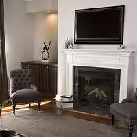 HGTV - living rooms - brown, gray, tufted, upholstered, chairs, black, caster, legs, white, fireplace, gray, brown, rug, green, velvet, drapes, gray walls, living room, TV over fireplace, Gloria Chair,