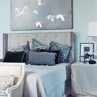 Domino Magazine - bedrooms - gray, tufted, wingback, headboard, silver, gray, bird, wall art, blue, gray, black, velvet, pillows, nailhead trim, linen, beige, French, settee, linen table, skirt, blue walls, bedroom, blue and gray bedroom, gray bedroom,