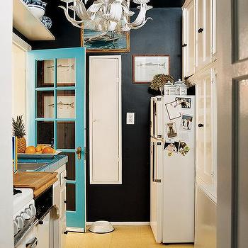 Domino Magazine - kitchens - hollywood regency chandelier, turquoise desk, turquoise blue door, black walls,  The chandelier is very similar