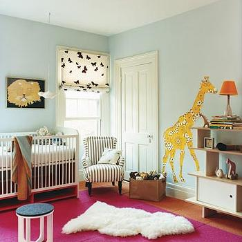 Domino Magazine - nurseries - wall mural, nursery wall mural, blue walls, blue wall paint, blue nursery colors, blue nursery paint colors, butterfly roman shades, nursery bookcase, hot pink rug, striped chair, black and white chair, black and white striped chair, Ikea Ludde,