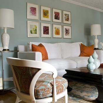 Angie Hranowski - living rooms - blue and orange living room, blue walls, white sofa, orange pillows, orange silk pillows, chinoiserie coffee table, lacquered coffee table, black lacquered coffee table, round end tables, art over sofa,