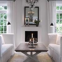 living rooms - gray, rustic, x-base, coffee table, fireplace, white, ruffled, slip-covers, slip-covered, sofas, iron, crystal, chandelier, black, wood, framed, mirror, black, floor, lamps, white, drapes, silver, candlesticks, parquet, wood, floors, monochromatic living room,