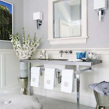 White mirror, sconces and gray ottoman.