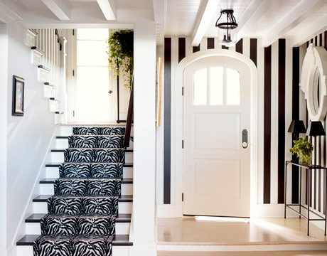 entrances/foyers - Sherwin Williams - black jack & decorator's white - stair runner, black and white stair runner, zebra stair runner, striped walls, vertical striped walls, black and white striped walls, black paint colors, arched door, arched front door, slim console table,