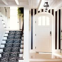 entrances/foyers - stair runner, black and white stair runner, zebra stair runner, striped walls, vertical striped walls, black and white striped walls, black paint colors, arched door, arched front door, slim console table,