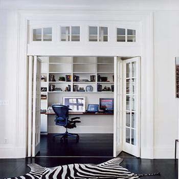 dens/libraries/offices - folding doors, glass folding doors, office folding doors, office with folding doors, office with glass doors, zebra rug, zebra cowhide rug, transom windows, office with transom windows,