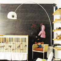 Domino Magazine - boy's rooms - accent wall, wood accent wall, plank accent wall, dark wood wall, dark wood accent wall, arc floor lamp, yellow shelves, floating yellow shelves, nursery, boys nursery,