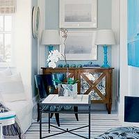 Suzanne Kasler - living rooms - turquoise, blue, beachy, mirrored, buffet, sideboard, console table, white, sofa, black, iron, mosaic, top, coffee table, turquoise, blue, lamps, art, round, pearl, mirror, striped, blue, white, rug, roman shades, blue, window, panel, blue walls,