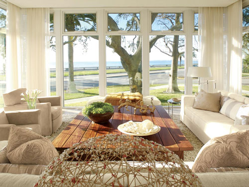 dantella: outside in  sunroom with white drapes, white sofas, rustic coffee table and pillows