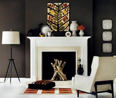 living rooms - brown, orange, ivory, cream, stone, fireplace, orange, geometric, rug, black, tripod, floor lamp, linen, wingback chair, art, Jonathan Adler vases, gray, decorative, plates, green, yellow, red leaf, art, floor, cushion, chocolate brown walls,