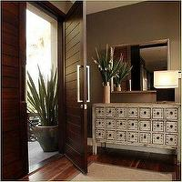 entrances/foyers - apothecary chest, foyer, foyer chest, taupe walls, taupe wall paint, paneled door,  modern entryway with apothecary chest