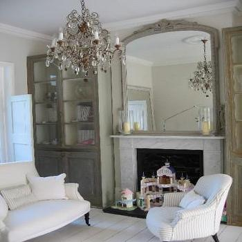 living rooms - distressed cabinets, living room cabinets, glass front cabinets, fireplace mirror, white marble fireplace, white plank floor, white painted floor,