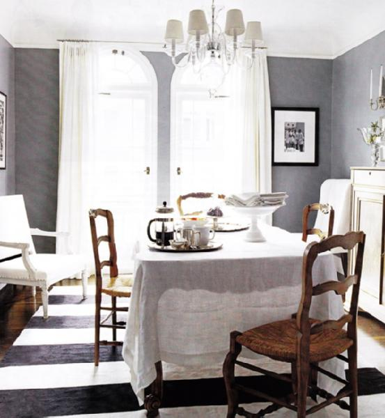 dining rooms - white gray brown dining table dining chairs French country charcoal gray white stripes striped rug white pedestal cake stand lucite acrylic chandelier art fireplace gray walls