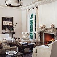 living rooms - cream gray, black, coffee table, brass, accent table, black, marble, granite, top, brown, rug, French, gray, taupe, velvet, sofa, cream, tufted, wingback, chairs, stone, fireplace, iron, chandelier, art, console table, cream walls, paint colors,