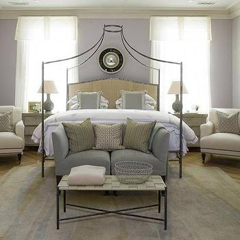 Phoebe Howard - bedrooms - iron bed, canopy bed, iron canopy bed, gray couch, gray sofa, sofa at foot of bed, lavender walls, valance, white valance,