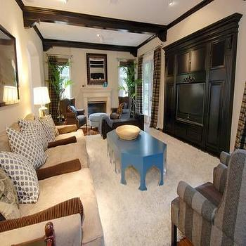 media rooms - blue coffee table, dark wood beams,  Tori Spelling  blue coffee table, sofa, striped gray wingback chair and exposed wood beams.