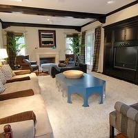 media rooms - sofa, black tv cabinet, coffee table, fireplace, mirror, beige, rug,  Tori Spelling  blue ocffee table, sofa, striped gray wingback