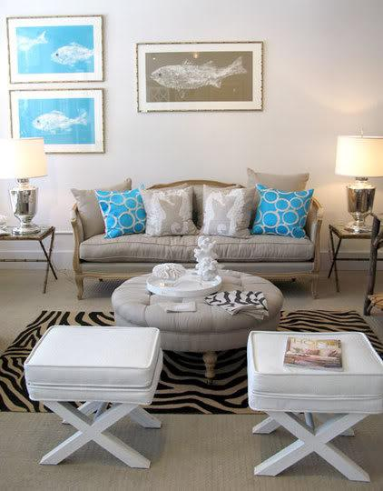 living rooms - White Crocodile X Bench taupe linen French sofa gray linen throw pillows turquoise blue circles throw pillows gray tufted round storage ottoman black cream zebra rug white faux leather gold faux bamboo tray tables silver urn lamps fish art soft gray walls