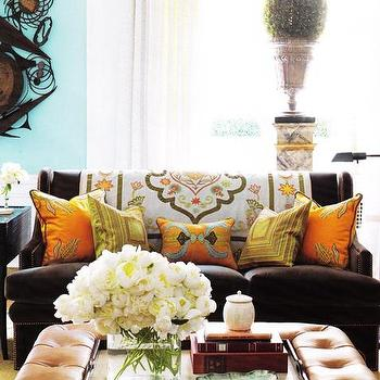 living rooms - brown, velvet, nailhead trim, tufted, sofa, curved arms, toffee, brown, leather, tufted, ottoman, tray, table, coffee table, citrine, yellow, rug, silk, orange, yellow, green, blue, throw pillows, white, silk, drapes, turquoise blue walls, suzani, throw,