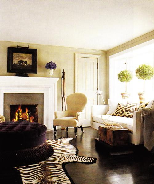 living rooms - purple beige tan black gray brown black cowhide zebra rug round purple tufted ottoman ribbon trim fireplace gray tiles modern white sofa gray geometric throw pillows topiary topiaries cream tufted accent chair wood trunk