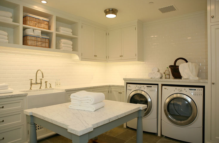 laundry/mud rooms - white carrara marble countertops counter tops island washer dryer farmhouse stainless steel sink faucet pulls knobs brushed nickel stone tile floors white brown laundry room