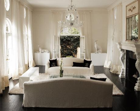living rooms - White living room, chandelier, drapery puddle, dark wood floor, long living room, modern french living room, slipcover sofas, slipcovered sofas, camelback sofas,