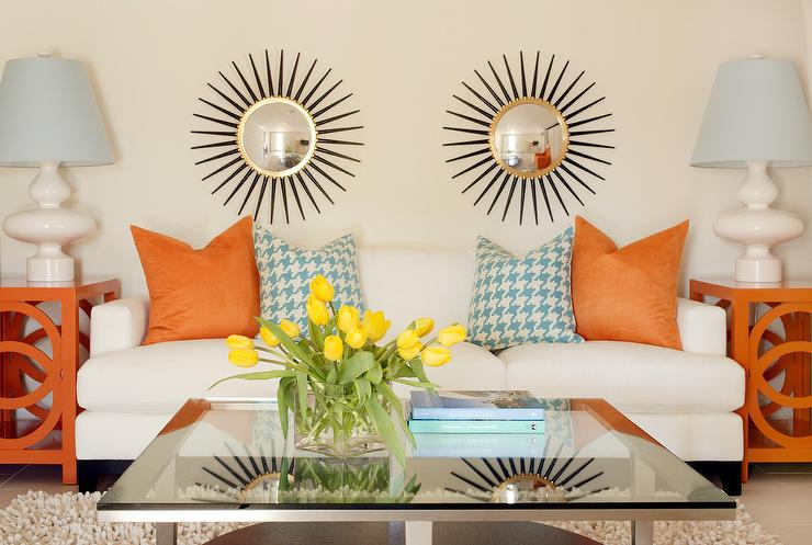 living rooms - silver starburst mirror orange pillows orange side tables baby blue houndstooth pillows white sofa glass top chrome coffee table white lamps baby blue lamp shades shag rug orange turquoise blue living room