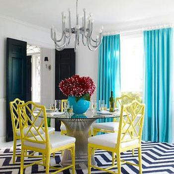 Jonathan Adler - dining rooms - teal drapes, teak curtains, teal window panels, teal blue drapes, teal blue curtains, teal blue window panels, teal silk drapes, turquoise silk curtains, teak silk window panels, yellow dining chairs, bamboo dining chairs, yellow bamboo chairs, powell dining table, glass top dining table, navy chevron rug, navy blue chevron rug, black double doors, Chippendale Chair, Herringbone Rug, Worlds Away Powell Dining Table,