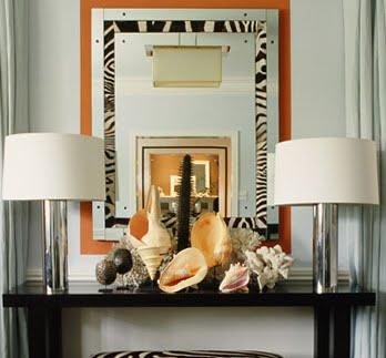 Gina Kates: Mary Mcdonald  polished chrome column lamps, glossy black console table and orange and ...