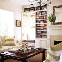 living rooms - brown, black, yellow, iron, chandelier, Asian, coffee table, slipcovered, white, sofas, sisal, rug, built-ins, bookshelf, bookshelves, cabinets, stripe, striped, citrine, yellow, white, throw pillows, fireplace, stone, tiles, gray, cushion, window seat,