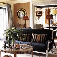 living rooms - grasscloth, wallpaper, blue, gold, porthole, mirror, silk, pleated, drapes, curtains, orange, black, brown, striped, throw, pillows, blue, velvet, French, sofa, round, wood, coffee table, tiled, floors, iron, candlesticks, lamp, floor, lamp,