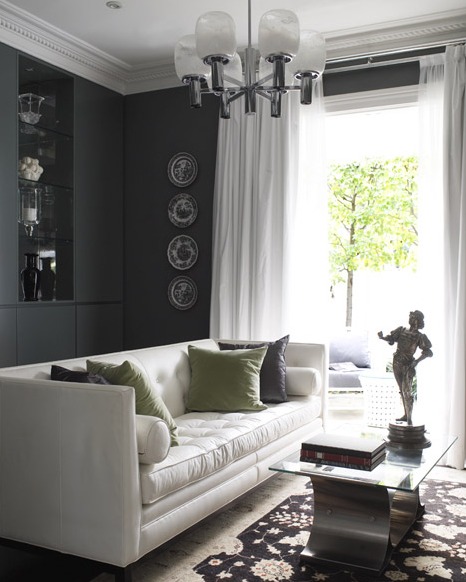 living rooms - white leather modern tufted sofa gray green velvet throw pillows modern glass-top stainless steel coffee table black white decorative plates wall art built-ins shelves cabinets black vase white silk drapes sheers curtains frosted glass chandelier crown molding charcoal gray walls