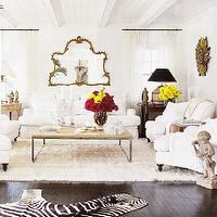 living rooms - ivory, cream, flokati, rug, white, black, cowhide, zebra, rug, white, slip-covered, sofas, chairs, iron, coffee table, wood top, stone, cherub, angel, statue, gold, ornate, mirror, gilt, sunburst, mirror, French, accent, tables, espresso, brown, wood, floors, white, cotton, drapes,