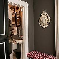 Taupe gray walls paint color, red bench, ivory cream mirror and wood floors.