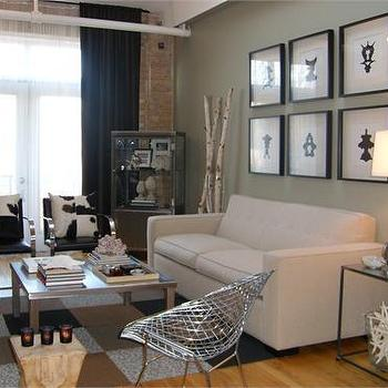 HGTV - living rooms - art gallery over sofa, art over sofa, art collection over sofa, black and white pillows, cowhide pillows, exposed brick wall, loft living room,