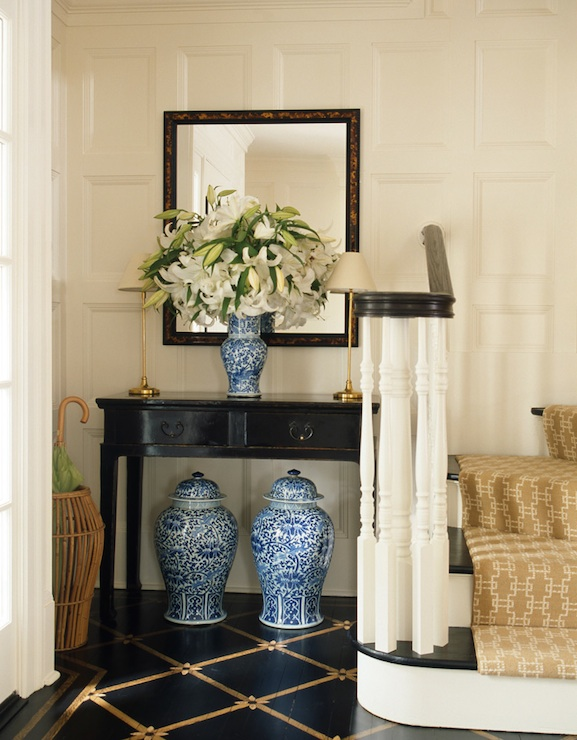 entrances/foyers - blue white ginger jars glossy black lacquer console table black gold diamond patterned floors wicker umbrella holder black gold mirror gold buffet lamps beige sand gold geometric stair runner entrance foyer entry