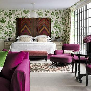bedrooms - purple chair, purple velvet chair,  Firmdale Hotels  Green wallpaper, tall headboard, purple chairs and ottoman and black pedestal