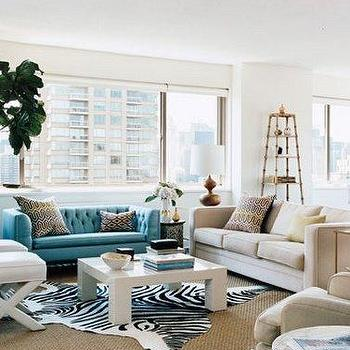 Domino Magazine - living rooms - x-bench, x-benches, turquoise sofa, turquoise blue sofa, turquoise tufted sofa, turquoise blue tufted sofa, white lacquer coffee table, zebra cowhide rug, faux croc bench, faux croc ottoman, etagere, brass etagere, antique brass etagere, fiddle leaf fig, Zebra Cowhide Rug, Crocodile Bench,