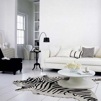 living rooms - white floors, white wood floors, plank floors, white plank floors, whitewashed floor, zebra rug, zebra cowhide rug, white sofa, contemporary white sofa, black slipper chair, black velvet chair, velvet slipper chair, round coffee table, black and white living room, black and white living room ideas, Zebra Cowhide Rug,