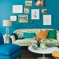 Domino Magazine - living rooms - peacock blue walls, peacock blue room, peacock blue living room, ikat sofa, upholstered sofa, patterned sofa, white and green sofa, white and green ikat sofa, slipper chair, peacock blue chair, peacock blue slipper chair, saarinen coffee table,