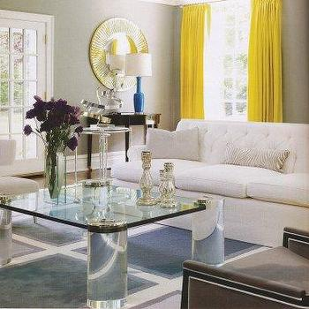 living rooms - yellow drapes, yellow curtains, lucite coffee table, square lucite coffee table, art deco coffee table, white sofa, white couch, white tufted sofa, white tufted couch, yellow window panels, yellow silk curtains, yellow silk drapes,