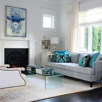 Style at Home - living rooms - blue sofa, blue velvet sofa, velvet sofa, turquoise pillows, turquoise blue pillows, acrylic coffee table, waterfall coffee table, living room fireplace, light blue walls, light blue paint, bergere chair, white bergere chair,