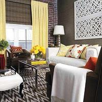 Style at Home - living rooms - yellow curtains, yellow drapes, yellow window panels, layered window treatments, brick wall, brick accent wall, white sofa, slipcovered sofa, parsons coffee table, metal coffee table, metal parsons coffee table, fretwork panels, fretwork wall panels,
