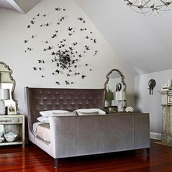 Kara Mann Design - bedrooms - gray bed, gray wingback bed, gray wingback headboard, gray velvet bed, gray tufted bed, butterfly art, butterfly sculpture, mirrors over nightstand, vaulted ceiling bedroom, bedroom with vaulted ceiling, Paul Villinski Butterfly Sculpture,
